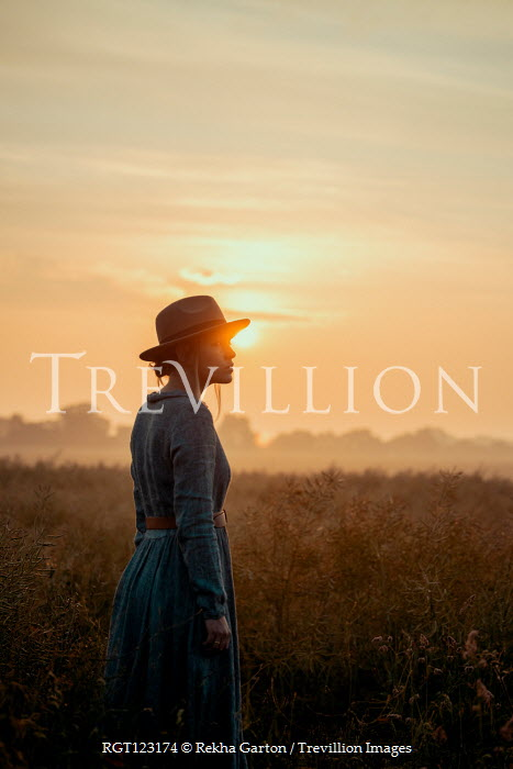 Rekha Garton WOMAN IN HAT STANDING IN COUNTRYSIDE WITH SUNSET Women