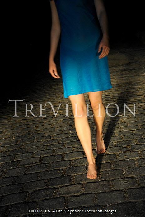 Ute Klaphake WOMAN WALKING BAREFOOT ON COBBLED STREET AT NIGHT Women