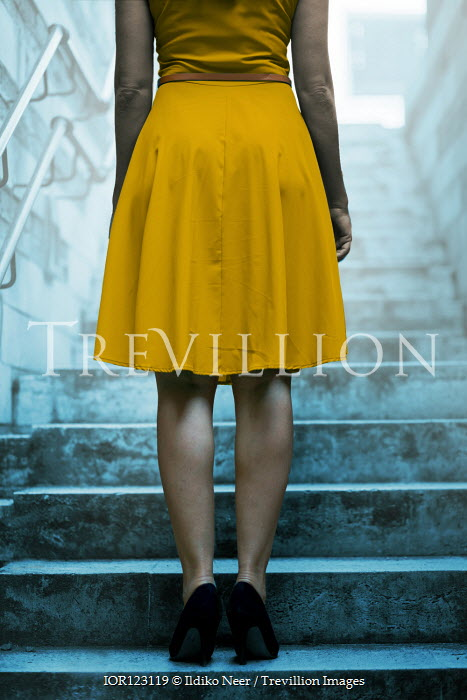 Ildiko Neer Yellow dress woman standing on stone steps