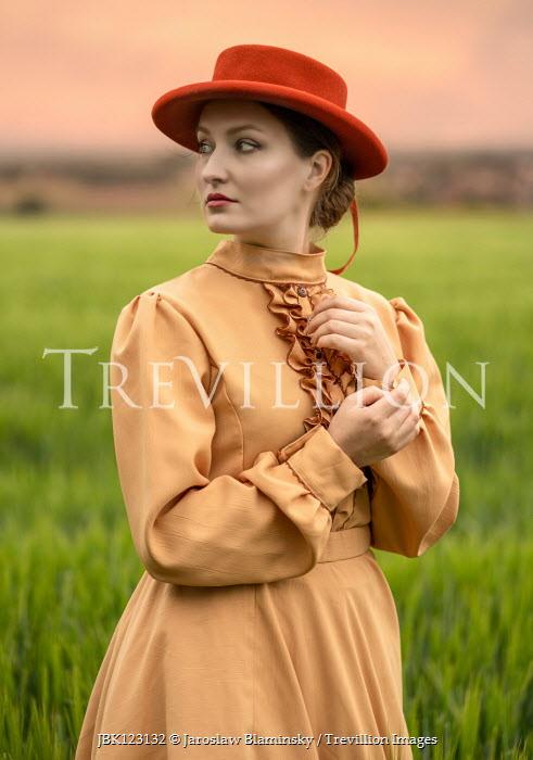 Jaroslaw Blaminsky WOMAN IN ORANGE DRESS AND HAT IN COUNTRYSIDE Women