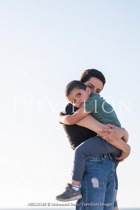 Mohamad Itani GIRL HUGGING LITTLE BOY OUTDOORS Children
