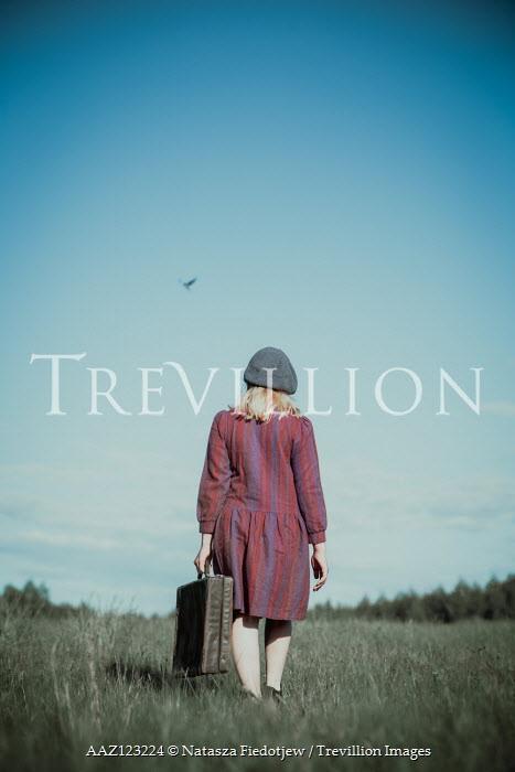 Natasza Fiedotjew Vintage girl with suitcase walking away in field