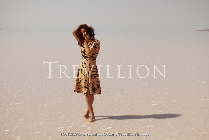 Esmahan Ozkan BRUNETTE WOMAN STANDING ON BEACH Women
