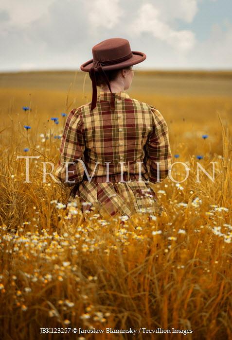 Jaroslaw Blaminsky WOMAN IN HAT STANDING IN FIELD WITH FLOWERS Women