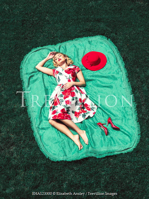 Elisabeth Ansley WOMAN IN FLORAL DRESS LYING ON RUG OUTDOORS Women