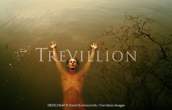 Daniil Kontorovich NAKED MAN FLOATING IN RIVER WITH REFLECTION OF TREE Men