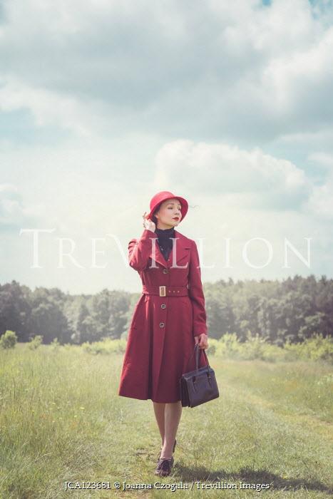 Joanna Czogala WOMAN IN RED HAT WALKING IN COUNTRYSIDE Women