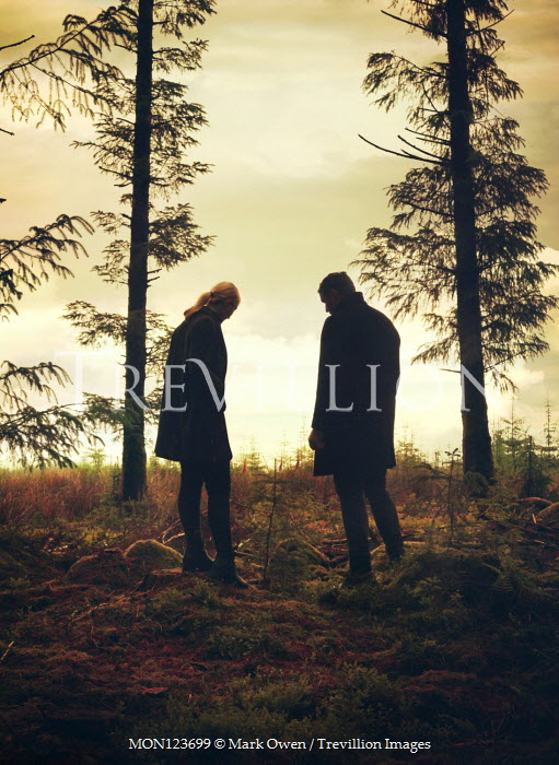 Mark Owen COUPLE IN COATS STANDING BY TREES IN COUNTRYSIDE Couples