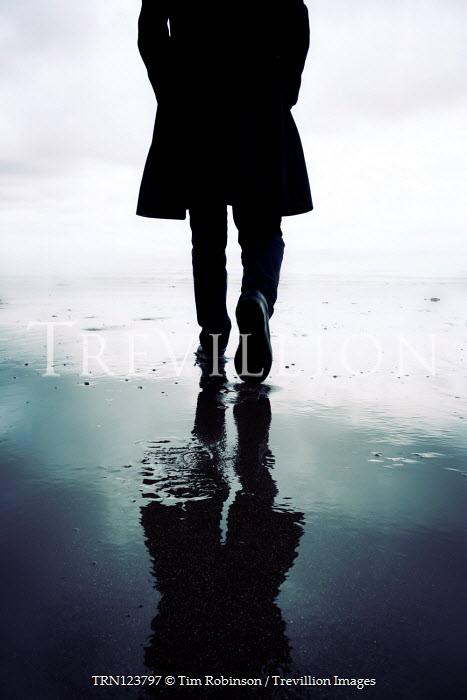 Tim Robinson SILHOUETTED MAN IN COAT WALKING ON BEACH Men