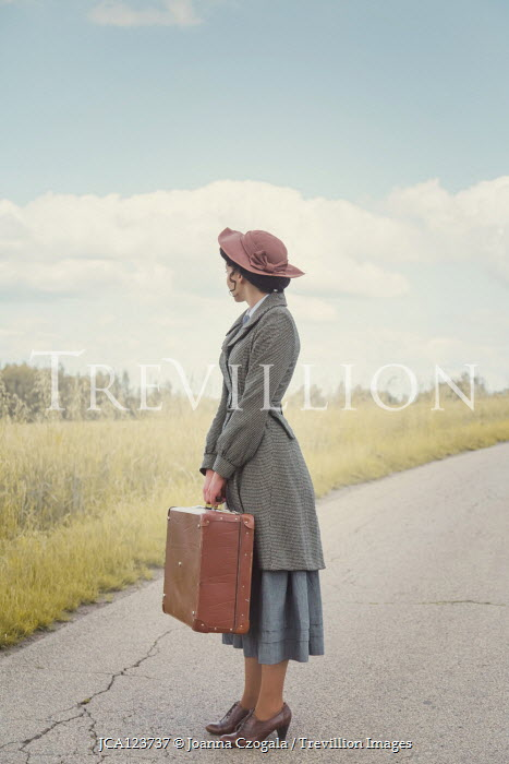 Joanna Czogala WOMAN CARRYING SUITCASE AND HAT ON COUNTRY ROAD Women