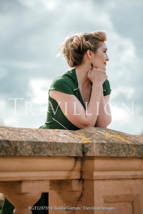 Rekha Garton BLONDE RETRO WOMAN LEANING ON WALL OUTDOORS Women