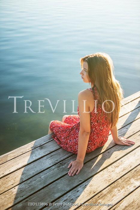 Terry Bidgood GIRL IN RED DRESS SITTING ON JETTY IN SUMMER Women