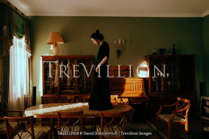 Daniil Kontorovich WOMAN STANDING ON DINING TABLE IN HOUSE Women