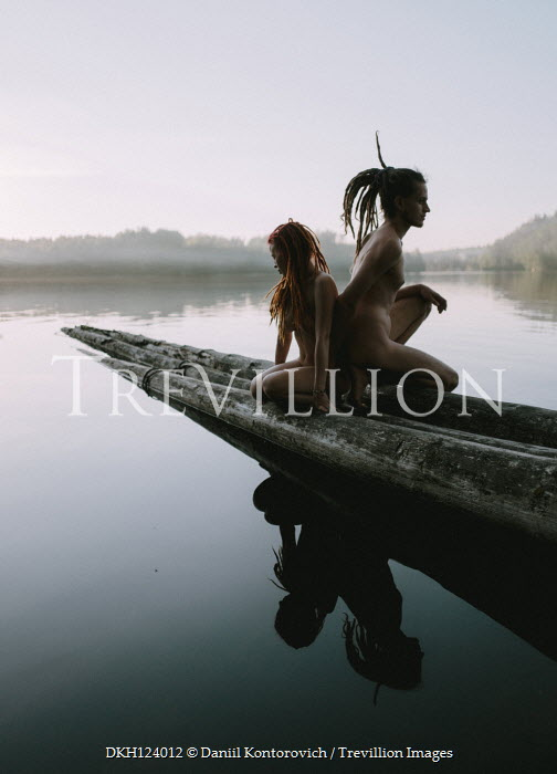 Daniil Kontorovich Naked couple with dreadlocks crouching on logs in lake