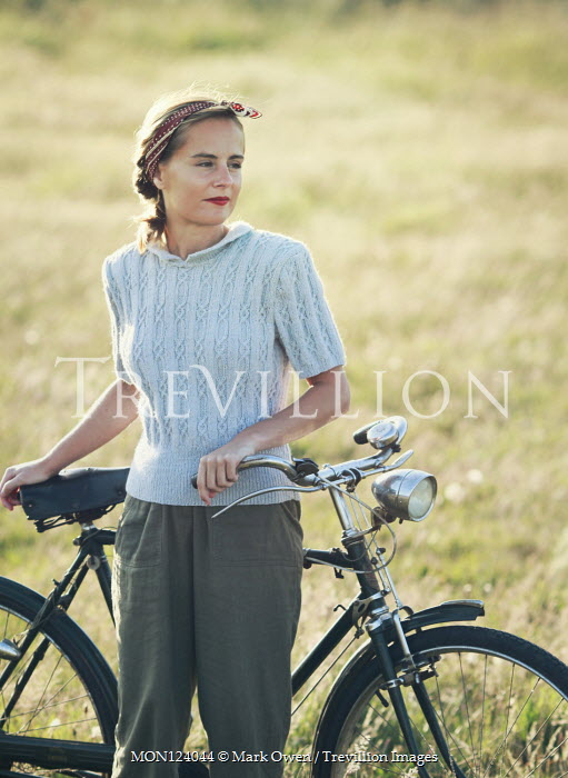 Mark Owen Young woman with bicycle in field