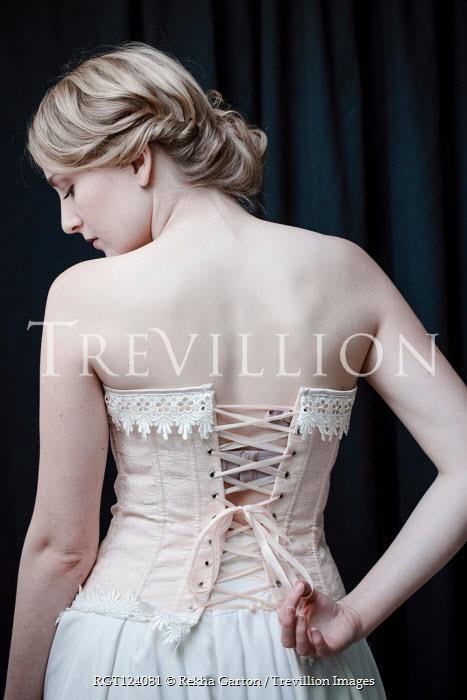 Rekha Garton Young woman untying Victorian corset