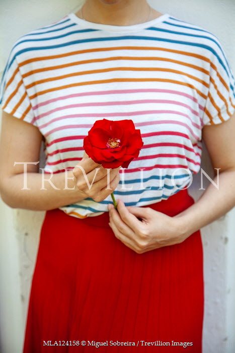 Miguel Sobreira Woman in striped top holding red rose