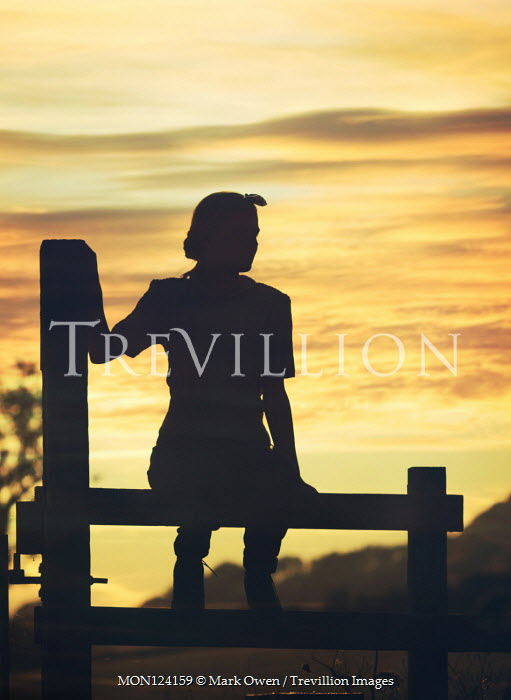 Mark Owen Silhouette of young woman sitting on fence at sunset