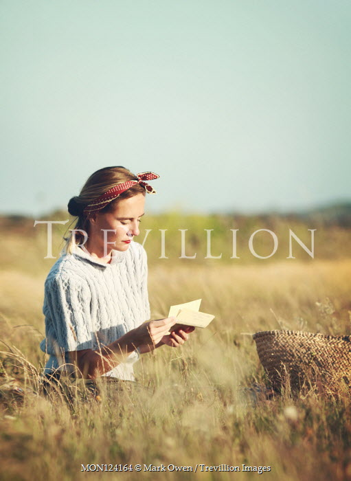 Mark Owen Young woman reading letter in field