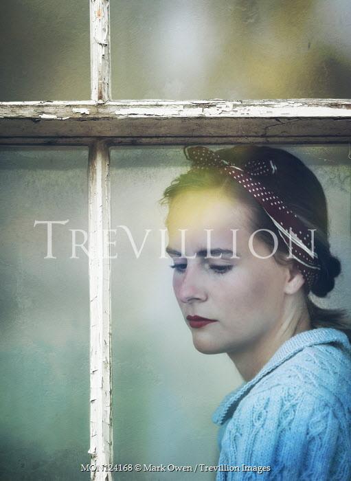 Mark Owen Young woman in 1940s bandana behind window