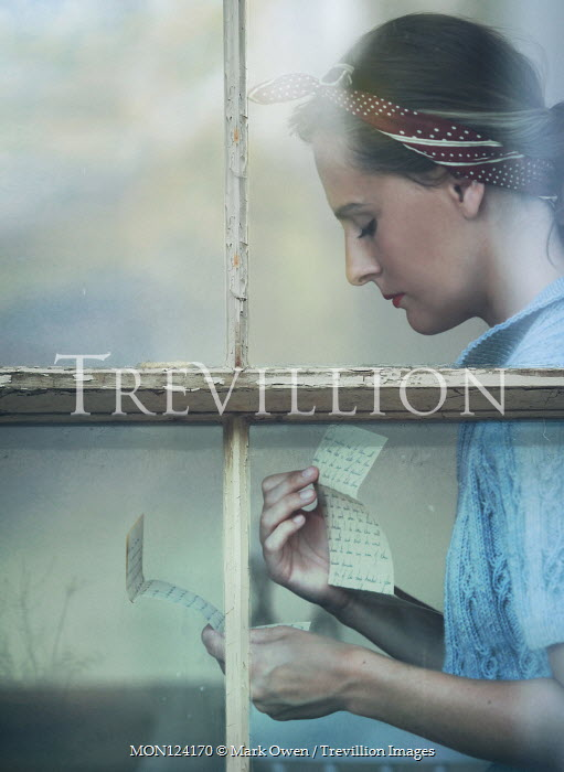 Mark Owen Young woman in 1940s bandana behind window reading letters