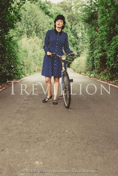 Shelley Richmond WOMAN IN SPOTTY DRESS WITH BICYCLE IN COUNTRYSIDE Women