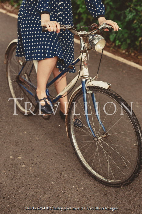 Shelley Richmond WOMAN IN SPOTTY DRESS RIDING BICYCLE ON ROAD Women