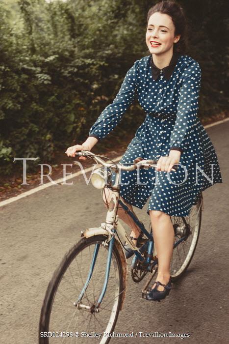 Shelley Richmond HAPPY WOMAN IN SPOTTY DRESS RIDING BICYCLE Women