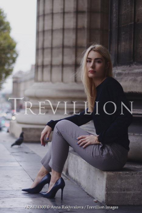 Anna Rakhvalova BLONDE WOMAN SITTING BY PILLAR OF CITY BUILDING Women