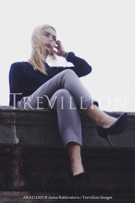Anna Rakhvalova BLONDE WOMAN IN STILETTOS SITTING ON WALL Women