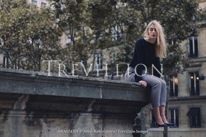 Anna Rakhvalova BLONDE WOMAN SITTING ON WALL IN CITY Women