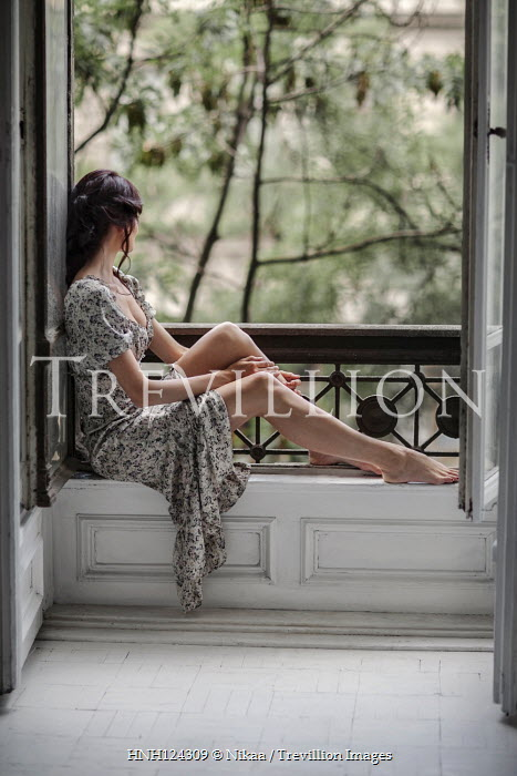Nikaa BRUNETTE WOMAN IN FLORAL DRESS SITTING BY BALCONY Women