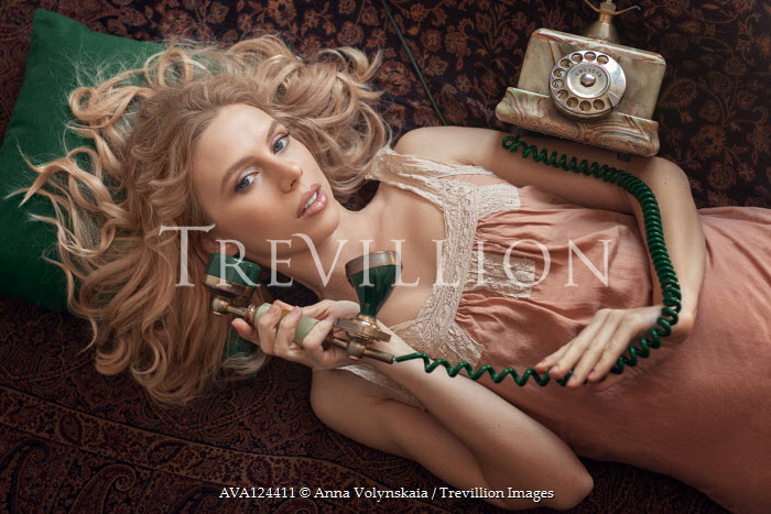 Anna Volynskaia BLONDE WOMAN WITH RETRO TELEPHONE LYING ON BED Women