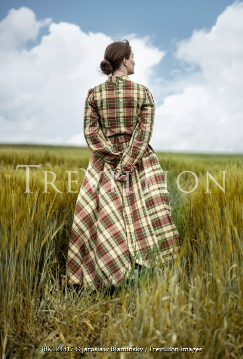 Jaroslaw Blaminsky WOMAN IN TARTAN GOWN STANDING IN WHEAT FIELD Women