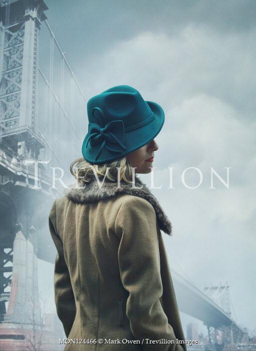 Mark Owen WOMAN IN HAT ND COAT STANDING BY BRIDGE Women