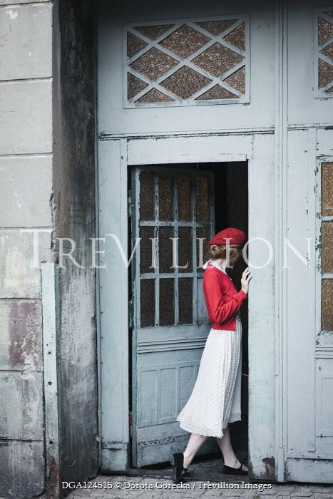 Dorota Gorecka Young woman with red beret standing in doorway