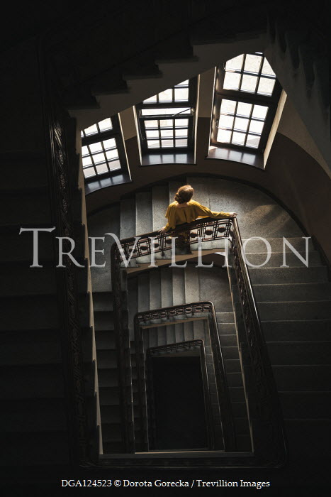 Dorota Gorecka Young woman in yellow dress standing on staircase from above