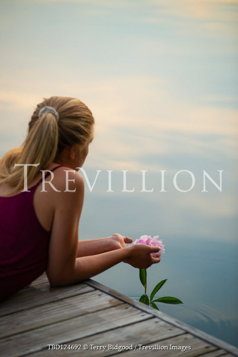 Terry Bidgood Young woman holding pink flower while lying on pier on lake