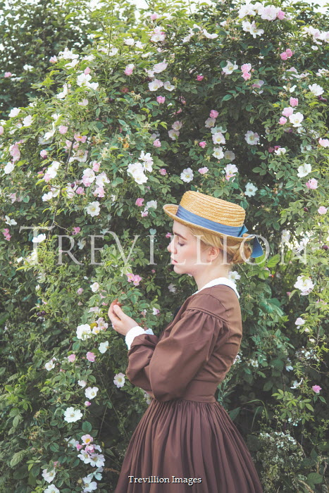 Joanna Czogala Young woman in Victorian dress and straw hat standing by hedge