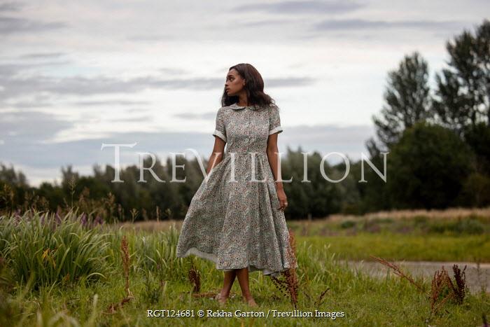 Rekha Garton Young woman in vintage floral dress in field
