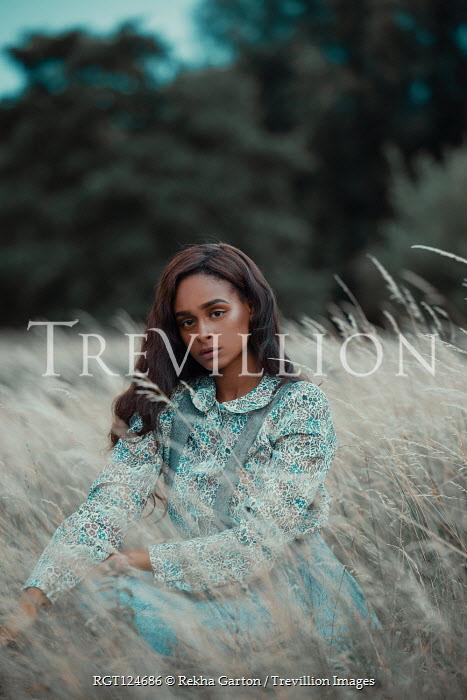 Rekha Garton Young woman in vintage dress crouching in field