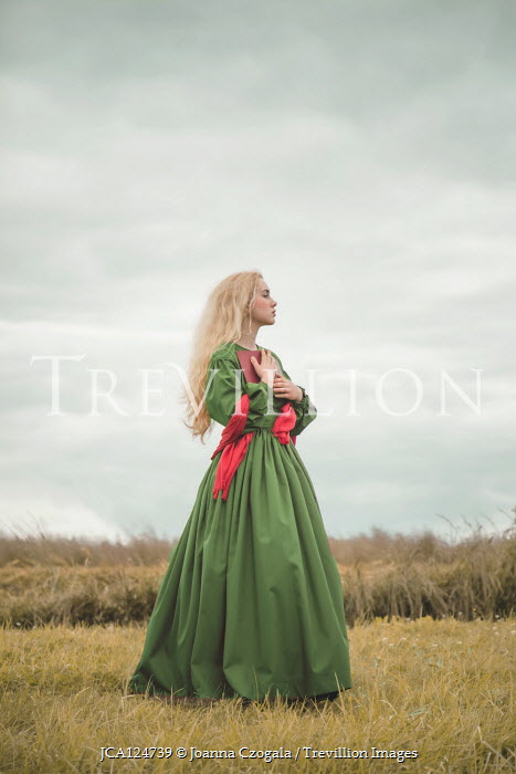 Joanna Czogala Young woman in green Victorian dress in field