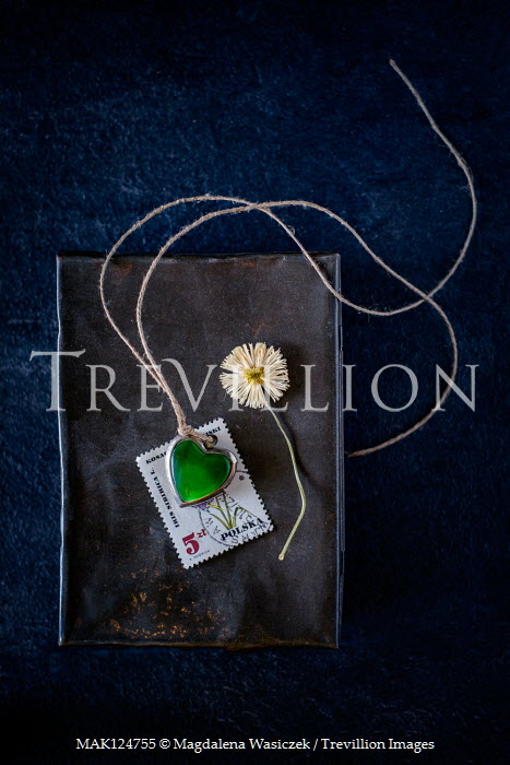 Magdalena Wasiczek Note book with green heart necklace, flower, and postage stamp