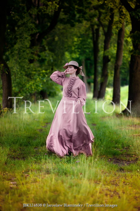 Jaroslaw Blaminsky Victorian woman in pink dress walking under trees
