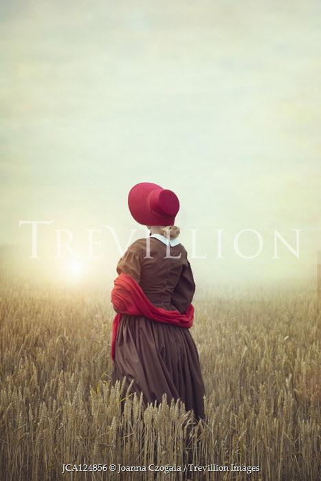 Joanna Czogala Victorian woman in bonnet standing in wheat field