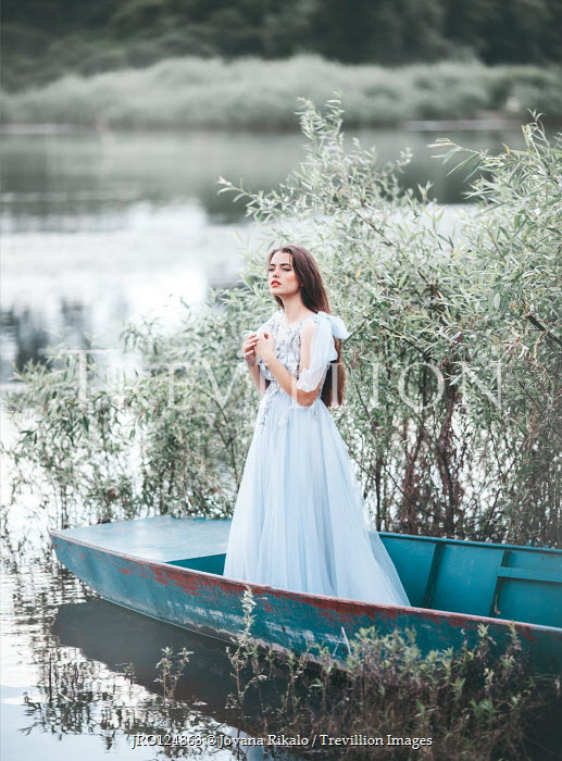 Jovana Rikalo Young woman standing in boat on lake
