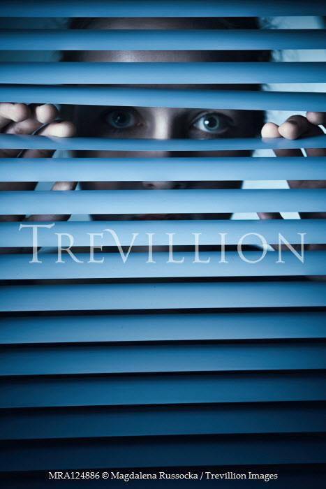 Magdalena Russocka woman staring behind blinds