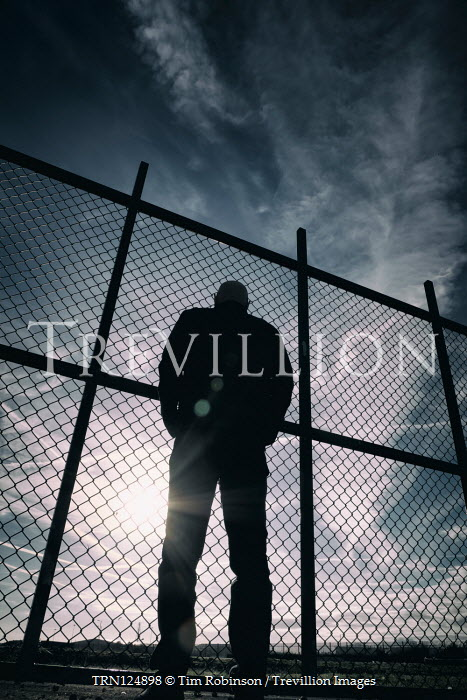 Tim Robinson Silhouette of man standing by chainlink fence at sunset
