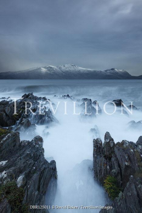 David Baker MISTY SEA AND ROCKS WITH SNOWY COASTLINE Seascapes/Beaches