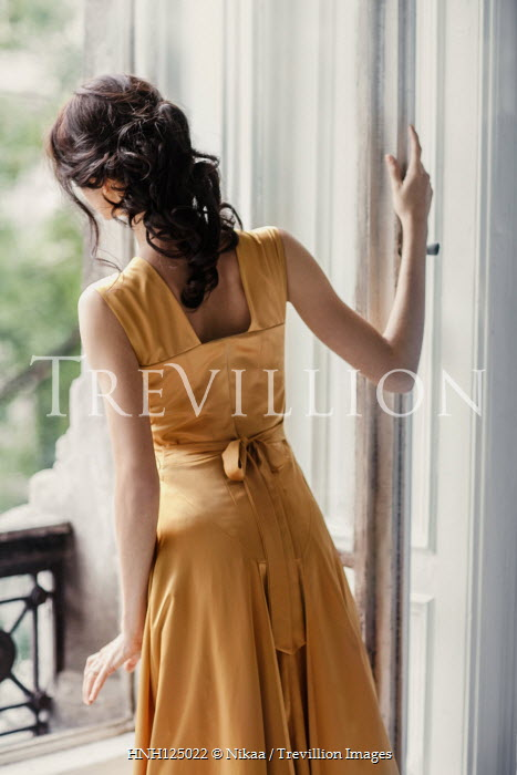 Nikaa BRUNETTE WOMAN IN GOLD DRESS WATCHING AT WINDOW Women